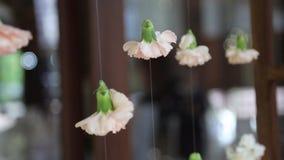 Flores em botão que penduram em linhas como a decoração do casamento filme