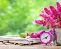 Flores en cubo, despertador rosado y libro Imagen de archivo