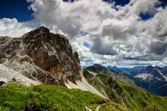 Flores en cuestas herbosas bajo pico rocoso en las montañas Italia de Carnic imágenes de archivo libres de regalías