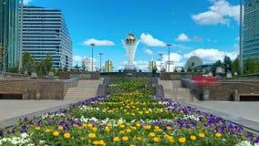 Flores en el bulevar de Nurzhol con Baiterek en hyperlapse del timelapse del fondo almacen de metraje de vídeo