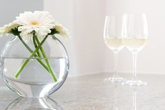 Flores en florero con el vino blanco en fondo Imagen de archivo libre de regalías