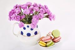 Flores en florero con los macarrones en el platillo Claveles y dulces Fotografía de archivo libre de regalías