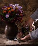 Flores en florero, las manos caucásicas del viejo hombre y la pila de monedas viejas Imagenes de archivo