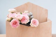 Flores en giftbox en fondo gris Ramo de rosas rosadas en caja de madera del sobre Copie el spase para el texto Imágenes de archivo libres de regalías