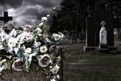 Flores en lápidas mortuorias en un cementerio Fotografía de archivo libre de regalías