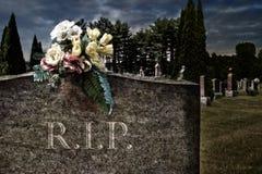 Flores en lápidas mortuorias en un cementerio Fotos de archivo libres de regalías