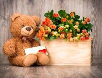 Flores en la caja y un oso de peluche Imágenes de archivo libres de regalías