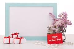 Flores en la carretilla y los regalos de las compras Fotos de archivo