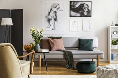 Flores en la tabla de madera delante del canapé debajo de los carteles en interior plano con la butaca Foto verdadera fotos de archivo libres de regalías