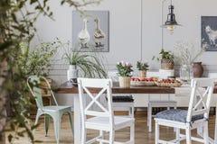 Flores en la tabla de madera en el interior blanco del comedor de la cabaña con los carteles y las sillas Foto verdadera fotografía de archivo