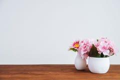 Flores en la tabla de madera y la pared blanca Fotos de archivo