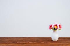 Flores en la tabla de madera y la pared blanca Fotografía de archivo