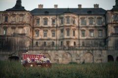 Flores en maleta contra el contexto del castillo antiguo Foto de archivo libre de regalías