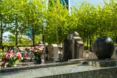 Flores en un cementerio con las piedras sepulcrales en fondo Fotos de archivo libres de regalías