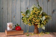 Flores en un florero con un libro Fotos de archivo libres de regalías