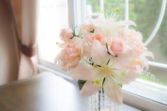 Flores en un florero de cristal en la tabla foto de archivo