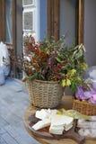 Flores en un florero y un queso en una placa cerca de un café de la acera en un anuncio Fotos de archivo