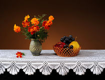 Flores en un florero y una fruta de cerámica Fotos de archivo libres de regalías