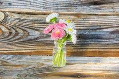 Flores en un tarro de cristal Margaritas en un tarro de cristal El fondo de los tablones viejos del pino con una textura pronunci Fotografía de archivo libre de regalías