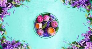 Flores en un vidrio en el medio de la tabla Imágenes de archivo libres de regalías