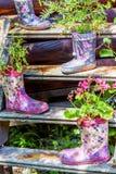 Flores en una bota floral de goma de la rodilla para la decoración del jardín Imagenes de archivo