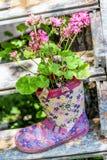 Flores en una bota floral de goma para la decoración del jardín Imagenes de archivo
