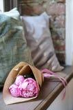 Flores envolvidas no papel de embalagem no fundo de matéria têxtil e na soleira de madeira fotos de stock