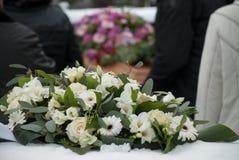Flores fúnebres brancas na neve antes de um caket imagem de stock