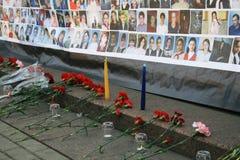Flores fúnebres cerca de un cartel con las imágenes de Fotografía de archivo libre de regalías