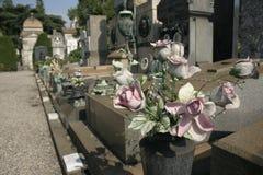 Flores falsas en la lápida mortuaria Fotos de archivo libres de regalías
