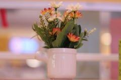 Flores falsas en un florero blanco Fotografía de archivo libre de regalías