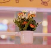 Flores falsas en un florero blanco Foto de archivo