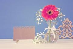 flores frescas ao lado do cartão vazio sobre a tabela de madeira Fotografia de Stock