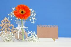 flores frescas ao lado do cartão vazio sobre a tabela de madeira Fotos de Stock