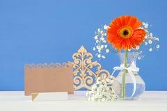 flores frescas ao lado do cartão vazio sobre a tabela de madeira Imagens de Stock