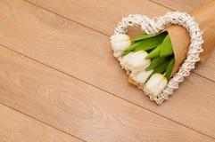 Flores frescas das tulipas e coração decorativo em pranchas de madeira Imagem de Stock Royalty Free