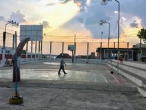 Flores, Guatemala - May 25th, 2018: a young boy playing basketball as the sun goes down in the small town of Flores, Guatemala. royalty free stock photo