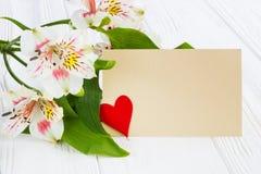Flores hermosas con la tarjeta de felicitación Imagen de archivo