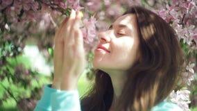 Flores hermosas el oler de la mujer en el jardín de la primavera almacen de metraje de vídeo