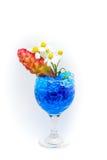 Flores hermosas en copa de vino con el hidrogel aislado en blanco Fotografía de archivo