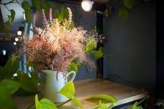 Flores hermosas en florero con la luz de la lámpara Foto de archivo