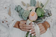 Flores hermosas en manos de las novias Ramo nupcial La mujer en casarse el vestido blanco se preparó para la ceremonia de boda Fo foto de archivo