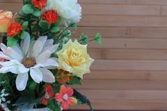 Flores hermosas en un florero en un fondo marrón de madera fotografía de archivo