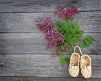 Flores hermosas y sandalias de la lila hechas de corteza Foto de archivo libre de regalías