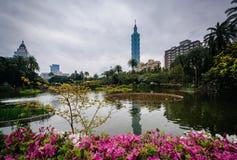 Flores, lago, e Taipei 101 no parque de Zhongshan, nos Di de Xinyi Imagem de Stock