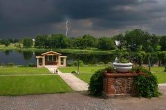 Flores, lago, jardín viejo y tormenta Fotografía de archivo