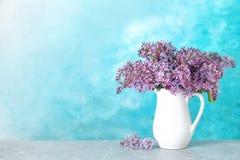 Flores lilás de florescência no jarro da porcelana na tabela contra o fundo da cor fotografia de stock