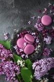 Flores lilás e macarons da amora-preta na placa do vintage sobre o gre Imagens de Stock