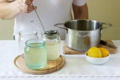 Flores más viejas, agua, limón y azúcar, ingredientes y una mujer que prepara un jarabe de la baya del saúco Estilo rústico fotografía de archivo
