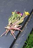 Flores marchitadas en la lápida mortuaria Foto de archivo libre de regalías
